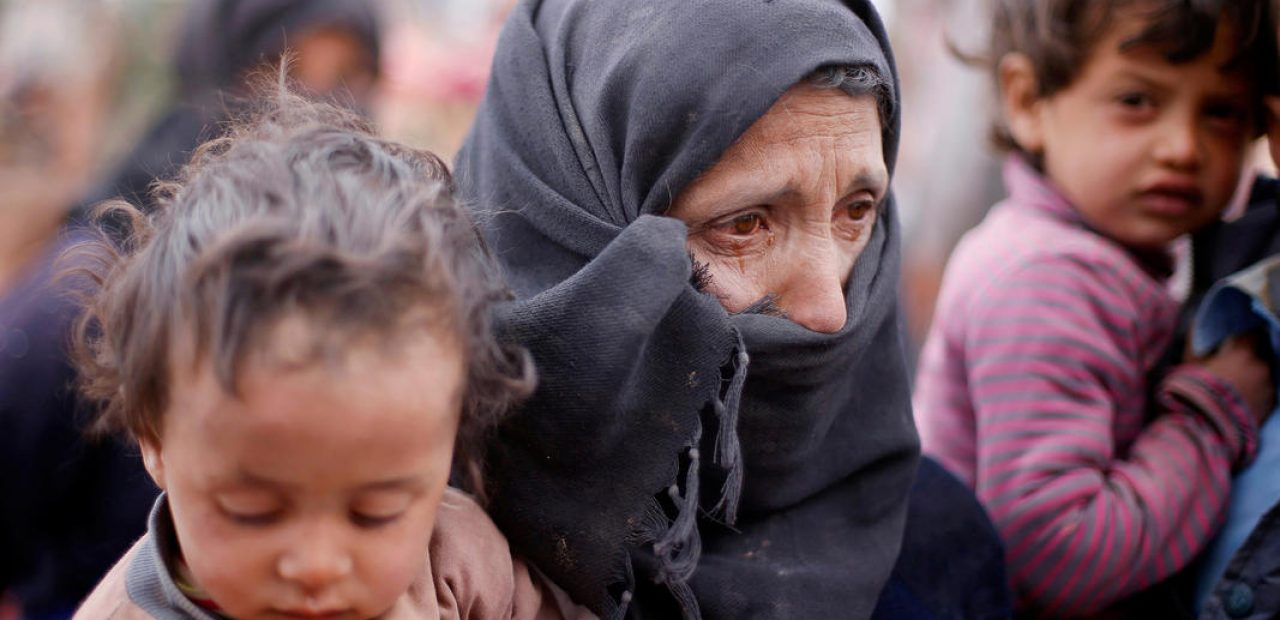 A Syrian refugee, who is stuck in between the Jordanian and Syrian borders, cries and holds her child as she waits to cross into Jordan after a group of refugees had crossed into Jordanian territory, near the town of Ruwaished at the Hadalat area, east of the capital Amman, May 4, 2016. REUTERS/Muhammad Hamed      TPX IMAGES OF THE DAY